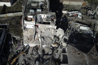 Rescuers search at a damaged building after a magnitude 6.4-magnitude earthquake struck.