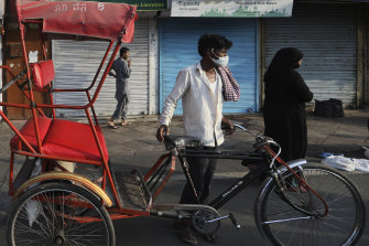 A rickshaw puller waits for customers in New Delhi.