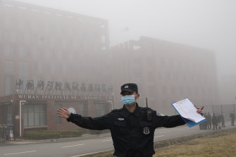 A security person moves journalists away from the Wuhan Institute of Virology in February after a World Health Organisation team arrived for a field visit in Wuhan in China's Hubei province.