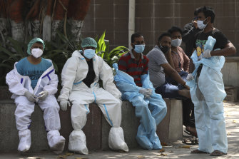 Health workers rest in between cremating COVID-19 victims in New Delhi, India.