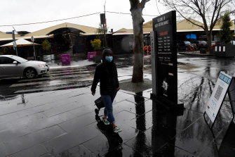 A shopper departs Queen Victoria Market during a break in the rain on Tuesday morning.