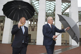 Hard rain: Josh Frydenberg and Prime Minister Scott Morrison in Canberra.