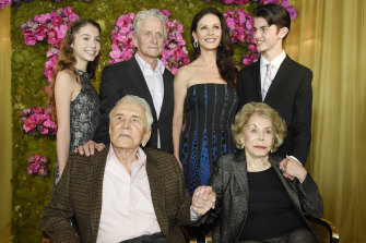 Kirk Douglas and his wife Anne in front of their son Michael, his wife Catherine Zeta-Jones and their children, Carys and Dylan, at Kirk's 100th birthday party at the Beverly Hills Hotel in 2016.