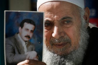 The father of assassinated senior Hamas military commander Mahmoud al-Mabhouh poses with a photograph of his son outside his family's house in February 2010.