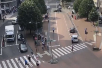 People run in the street after hearing gunshots in Liege, Belgium.