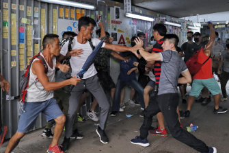 A group of pro-police supporters fight with an anti-government protester, right, outside the Amoy Plaza in the Kowloon Bay district in Hong Kong, Saturday, September 14, 2019.