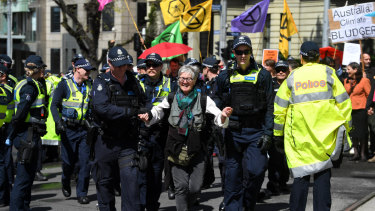 An Extinction Rebellion activist is arrested during a protest in Melbourne on Tuesday.