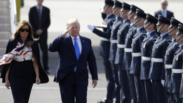 President Donald Trump salutes an honour guard as he and first lady Melania Trump arrive at Stansted Airport in England.