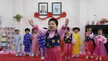 Children in traditional Korean dress perform for visitors under the photos of Kim Il-song and Ho Chi Minh at a kindergarten in Hanoi.