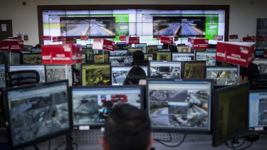 A control room of camera feeds and workers, part of Ecuador's Emergency Response System.