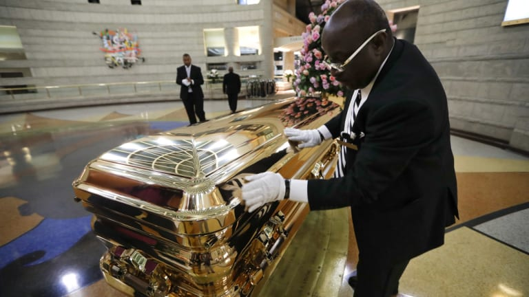 Vincent Street polishes the casket of the legendary Aretha Franklin.