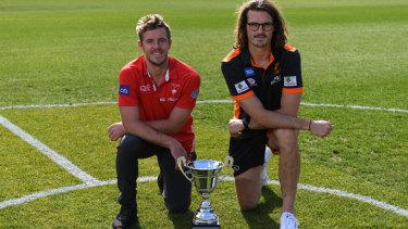 Swans co-captain and Giants co-captain Phil Davis pose with the Sydney AFL derby trophy.