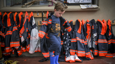 Cooper, from Diamond Creek Memorial Kindergarten, gets into his wet-weather clothing. Every child at the kindergarten is provided with winter gear.