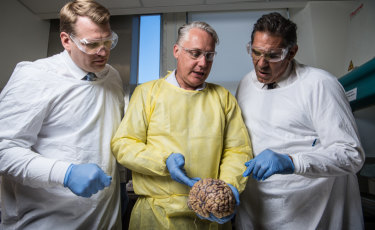 Chris Nowinski from Concussion Legacy Foundation, Michael Buckland of RPA and former NFL player Colin Scotts examine a brain.