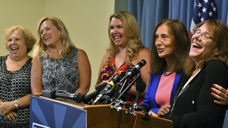 A winner exposed: Mavis Wanczyk, right, of Chicopee, Massachusetts., laughs beside state treasurer Deb Goldberg during a news conference where she claimed the $US758.7 million Powerball prize at Massachusetts State Lottery headquarters in August 2017, in Braintree, Massachusetts.