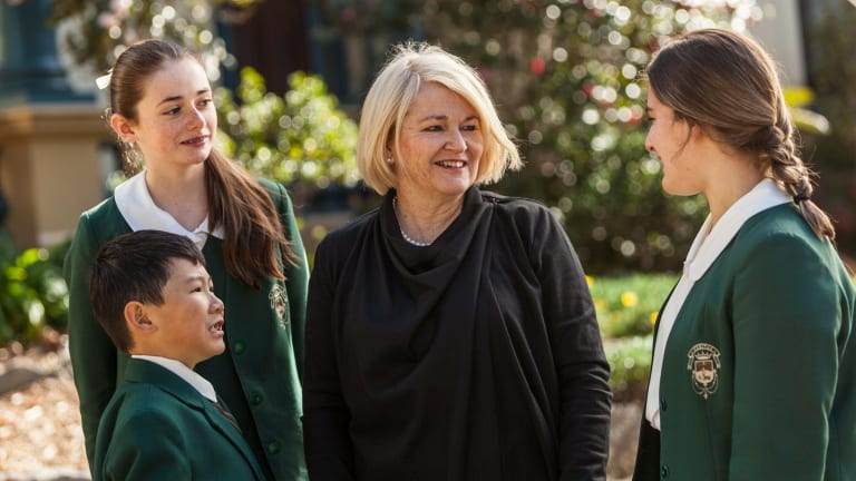 Dr Maree Herrett, principal of Santa Sabina College, with students wearing the green uniforms in 2016.
