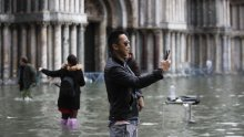 Tourists take pictures in a flooded St. Mark's Square. The crypt beneath St. Mark's Basilica was inundated for only the second time in its history.