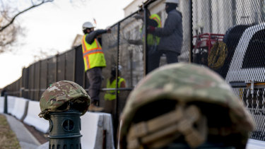 National Guard helmets sit on top of barricades as workers install razor wire to fences on Capitol Hill on Thursday.