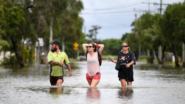 Local residents wade through flood water in the suburb of Hermit Park in Townsville