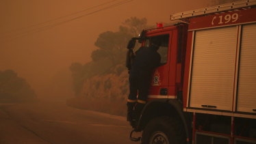 A fire truck is engulfed in a pall of orange smoke on a road near Kineta, west of Athens.