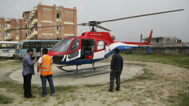 Hospital officials get ready to unload the dead body of a plane crash victim outside the Teaching Hospital in Kathmandu, Nepal, on Sunday.