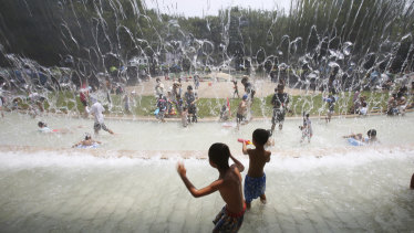 Children play in a Tokyo park on Monday as the mercury reached 35 degrees.
