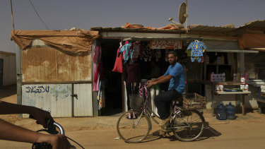 A Syrian man rides his bike past shops on the main shopping street, the 'Shams Elysee' in Zaatari camp.