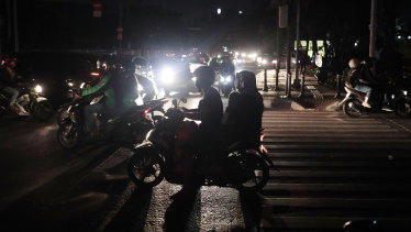 Motorists navigate through traffic during a power outage in Jakarta.