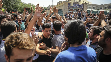 A group of protesters chant slogans at the main gate of the Old Grand Bazaar, in Tehran, Iran in 2018.