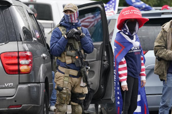 One supporter of President Trump holds a gun as another a baseball bat in front of the Oregon State Capitol building.