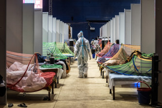 A medical worker in PPE observes patients who have been infected by COVID-19 inside a makeshift facility in a New Delhi sports stadium.