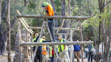 ACT Parks and Conservation staff work with volunteers to restore Tidbinbilla Hut, a site used for decades as a camping and picnic area before it fell into disrepair.