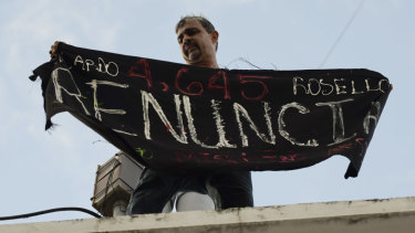 "Activist Alberto de Jesús Mercado holds a banner that reads in Spanish ""Resign""."