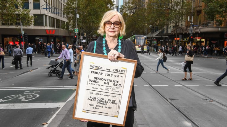 Proud and passionate: activist Jean McLean, pictured in Collins Street, holds a poster for a Wreck the Draft event from her anti-Vietnam War conscription protest days.