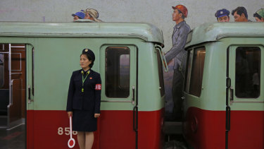 A North Korean subway officer stands next to a train in a subway station in Pyongyang.