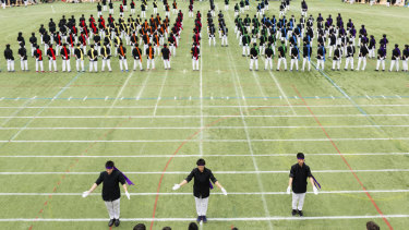 Colour-coded teams prepare for a botaoshi tournament at the Kaisei Gakuen school's annual festival in Tokyo.