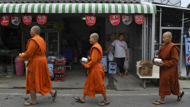 A woman watches female monks pass by her shop on their morning alms rounds.