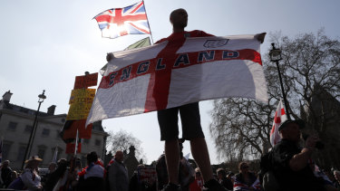 A Brexit supporter holds an England flag at Parliament Square in Westminster, London.