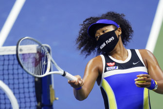 Naomi Osaka, wearing a mask in tribute to George Floyd, fires a ball in celebration after beating Shelby Rogers.