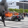 A police car burns during protests in Los Angeles.