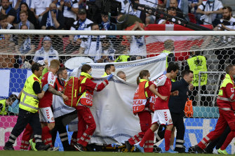 Denmark's Christian Eriksen is taken away on a stretcher after collapsing on the pitch during the Euro 2020 soccer championship group B match between Denmark and Finland.