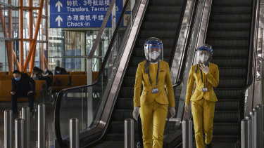 BEIJING, CHINA - MARCH 24: Chinese tourist information clerks wear protective masks and visors as they walk in the arrivals area at Beijing Capital International Airport.