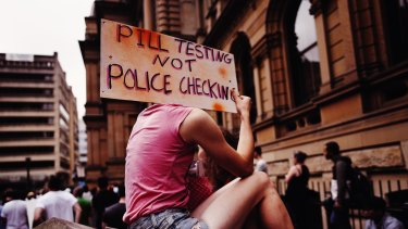 An attendee holds up a sign at a pill testing rally held at Sydney's Town Hall this year.