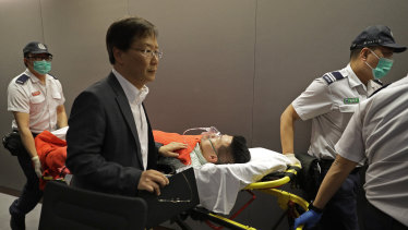 Pro-democracy lawmaker Gary Fan is carried on a stretcher after being injured in a clash with pro-Beijing lawmakers at a controversial amendments meeting in Hong Kong on Saturday.