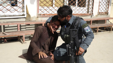 An Afghan policeman comforts a man after an attack on a maternity hospital in Kabul, Afghanistan.
