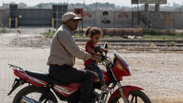 A man drives his motorbike with his daughter in the Turkish side of the border between Turkey and Syria on Wednesday.