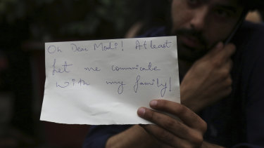 A Kashmiri, who works in Bangalore, holds a piece of paper addressing Indian Prime Minister Narendra Modi during a protest in Bangalore.