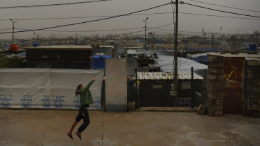 A boy runs along a street in Basirma refugee camp.