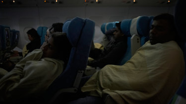 Trying to sleep in an economy class cabin.