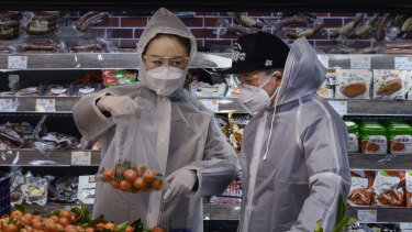 A Chinese couple wears plastic coats and protective masks as they shop for groceries at a supermarket in Beijing on February 11.
